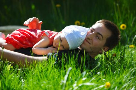 Adorable baby girl and young father outdoors at sunny summer day photo
