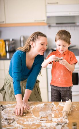 Young mother and son in kitchen making cookies. photo