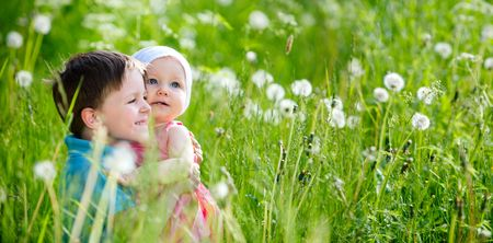 Brother and little sister playing in green grass at sunny summer day. photo