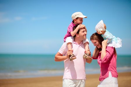Young happy family with two kids on beach vacation photo