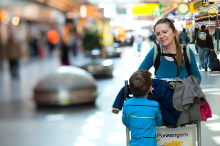 Young mother and son with luggage cart at airport  photo