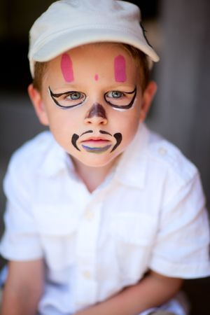 Small boy having his face painted as a pirate photo