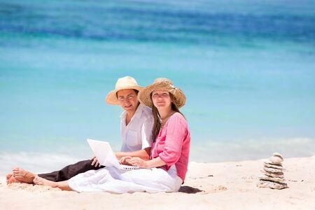 Happy couple using laptop on the beach photo