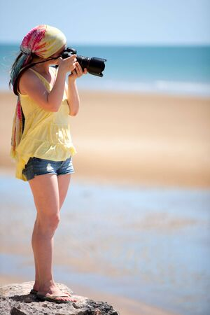 Beautiful young female photographer taking pictures on beach photo