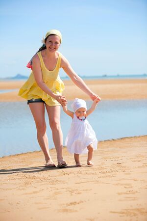 Young mother and baby girl walking on the beach photo