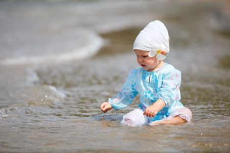 Cute baby girl with tropical flower on the beach photo