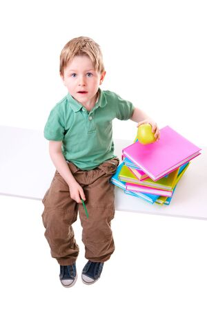 Back To School. Little boy with books isolated on white background photo