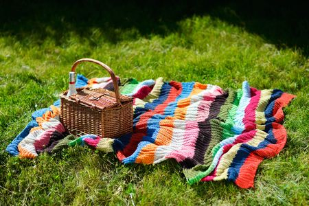 Picnic basket and colorful blanket on green grass at sunny day photo