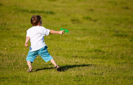 watergun: Small boy having fun outdoors at sunny summer day