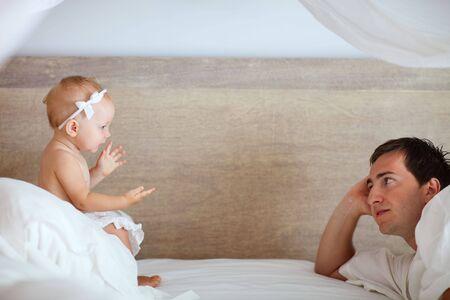 padres hablando con hijos: Padre joven y ni�a linda hablando unos con otros en la cama Foto de archivo