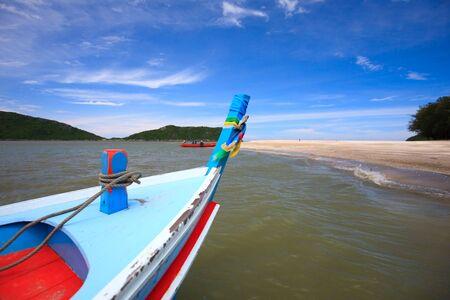 Traditional Thai longtail boat near tropical white sand beach photo
