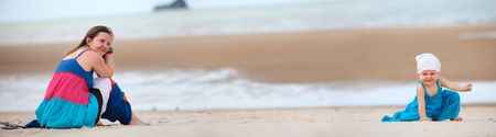 Panoramic photo of young mother and baby girl on the beach photo