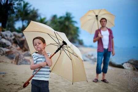 Father and son on the beach at rainy evening photo