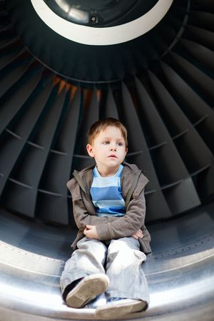 Boy sitting inside aircraft turbine photo