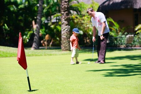 Father and son playing golf. Focus on flag. photo