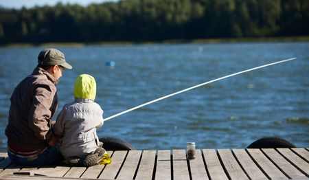 weekends: Father and small son fishing together on lake
