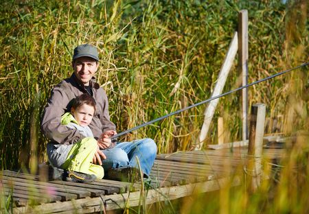 Father and small son fishing together on lake photo
