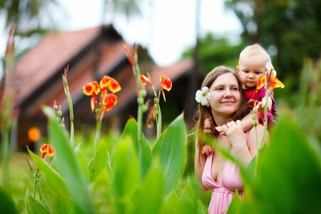 Lifestyle portrait of young mother and baby daughter outdoors Stock Photo
