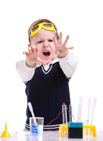 Young boy performing chemistry experiments with different liquids. photo