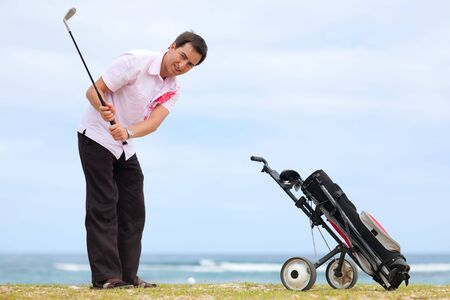 Young man playing golf at tropical golf course close to ocean photo