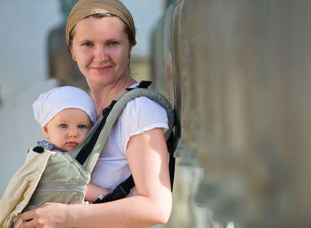 draagdoek: Lifestyle portret van de jonge moeder en dochter buiten in baby carrier