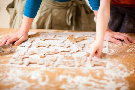 Young mother and son in kitchen making cookies photo