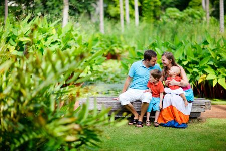 Young family with two kids having fun outdoors at sunny summer day photo