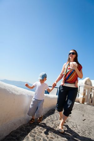 sling: Family trip to Europe. Young mother with two kids exploring Greek town. Stock Photo