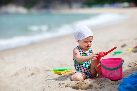 Cute baby girl playing with beach toys on tropical beach photo