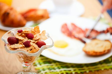 Delicious breakfast. Corn flakes with berries, fried egg, bacon, toast, croissants, juice and fresh coffee. Stock Photo - 5498060