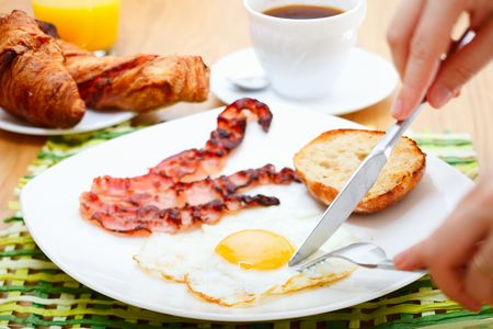 Delicious breakfast. Fried egg, bacon, toast, croissants, juice and fresh coffee. Stock Photo - 5498061