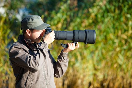 Young nature photographer with taking photos using telephoto lens photo