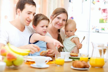 Young happy family with two kids having breakfast together photo