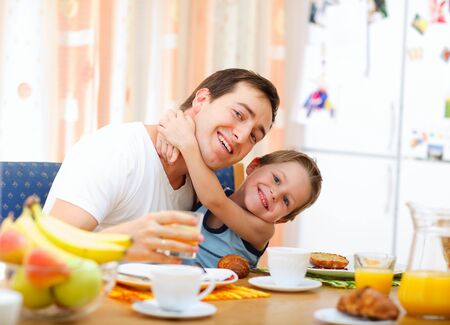 Young happy father and son having breakfast together photo