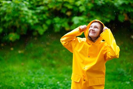 Happy young woman in yellow raincoat under rain Stock Photo - 5528490
