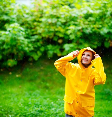 rainy season: Happy young woman in yellow raincoat under rain Stock Photo