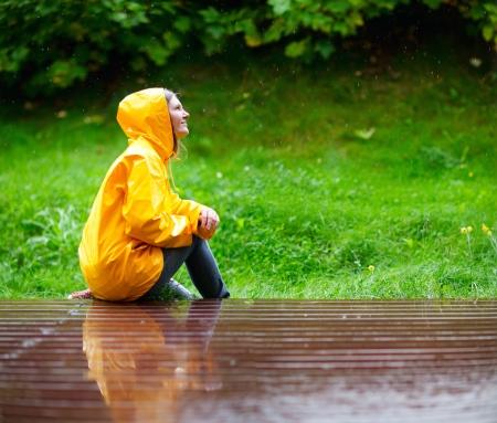 rain coat: Happy young woman in yellow raincoat under rain Stock Photo