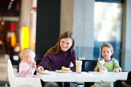 Young mother with two kids enjoying meal sitting at cafe photo