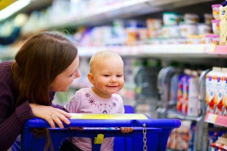 Young mother with baby daughter shopping in supermarket Фото со стока