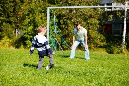 jugando futbol: Padre e hijo jugando al f�tbol al aire libre en d�as soleados