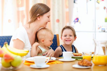 mealtime: Young happy mother and two kids having breakfast together Stock Photo