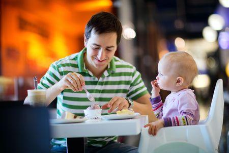 hombre comiendo: El padre de la hija de disfrutar de la comida del beb� sentado en el caf� de Foto de archivo