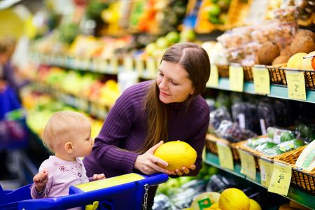 supermarket trolley: Young mother with baby daughter shopping in supermarket Stock Photo