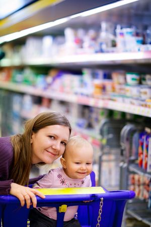 Young mother with baby daughter shopping in supermarket Stock Photo - 5559259