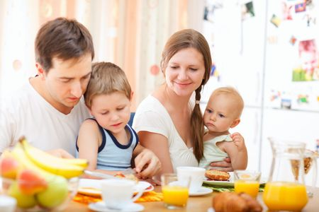woman eat: Young happy family with two kids having breakfast together