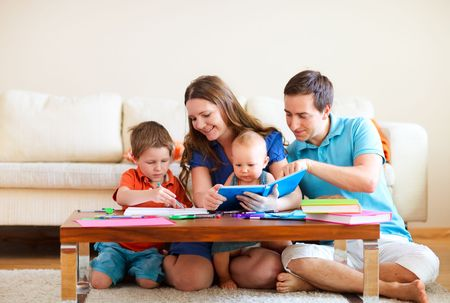 kids drawing: Young happy family with two kids drawing and reading together
