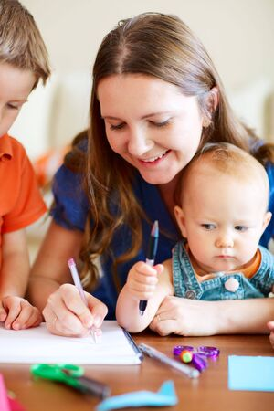 Young mother and her two kids drawing together. Can be used also in kindergarten/daycare context. Stock Photo - 5559289