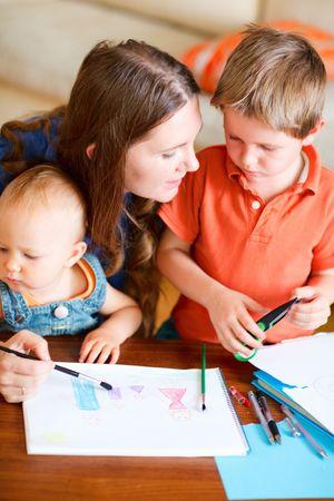 mother to be: Giovane madre ei suoi due bambini di disegno insieme. Pu� essere utilizzato anche nella scuola materna  asilo nido contesto.