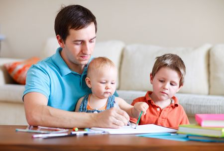 Young father and his two kids drawing together photo