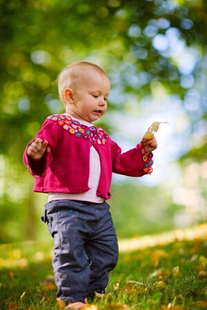 Cute 1 year old baby girl walking outdoors